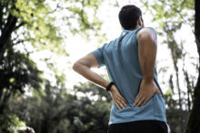 Man feeling backache at a park