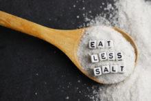 Eat less salt advice written with plastic letter beads on granulated salt