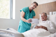 Surgeon With Digital Tablet Visiting Senior Male Patient In Hospital Bed In Geriatric Unit