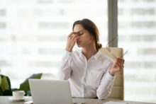 Fatigued businesswoman taking off glasses tired of computer work
