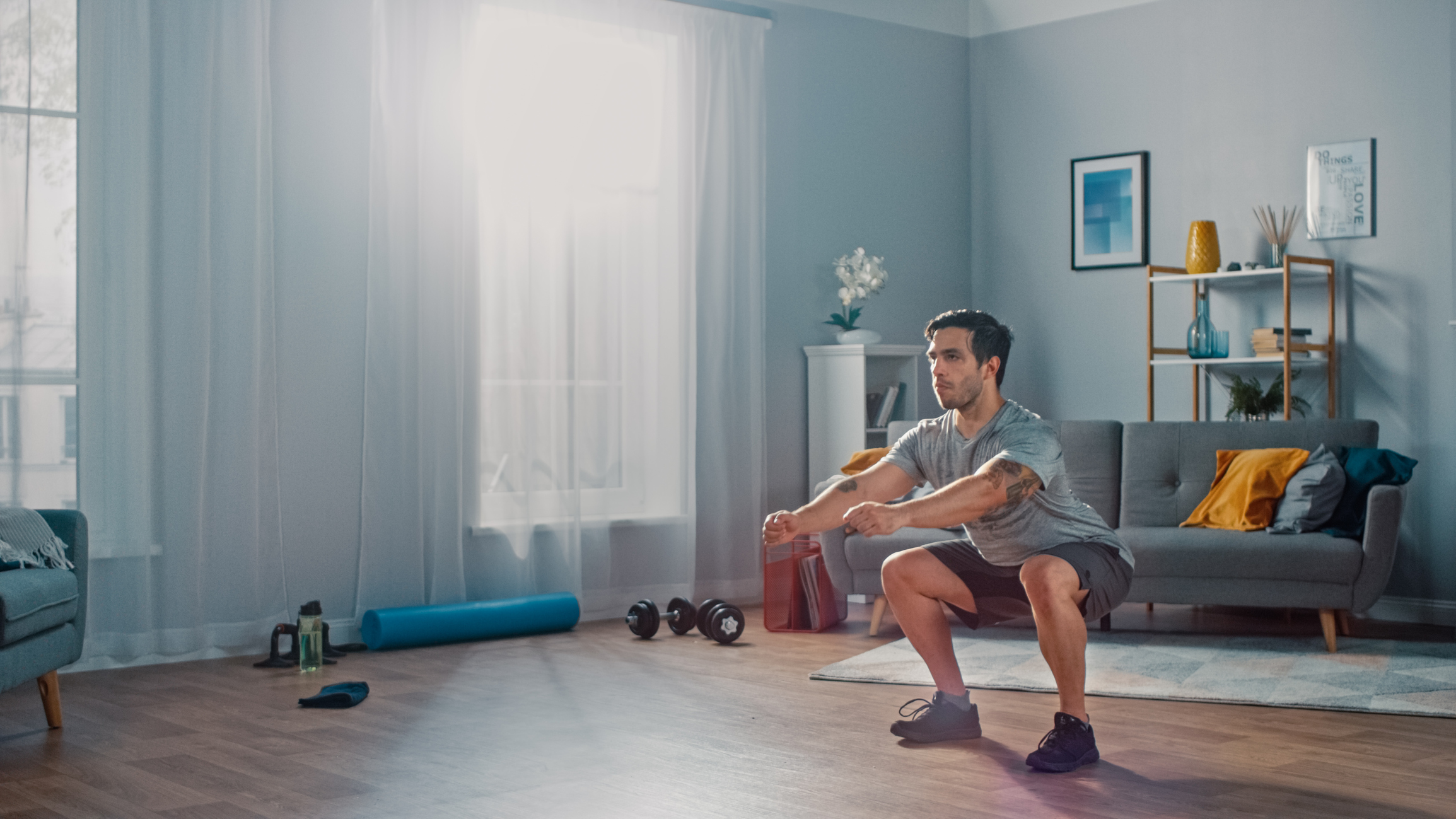 man performing squats in his home gym