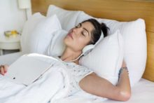 Woman trying to listen to music to help sleep