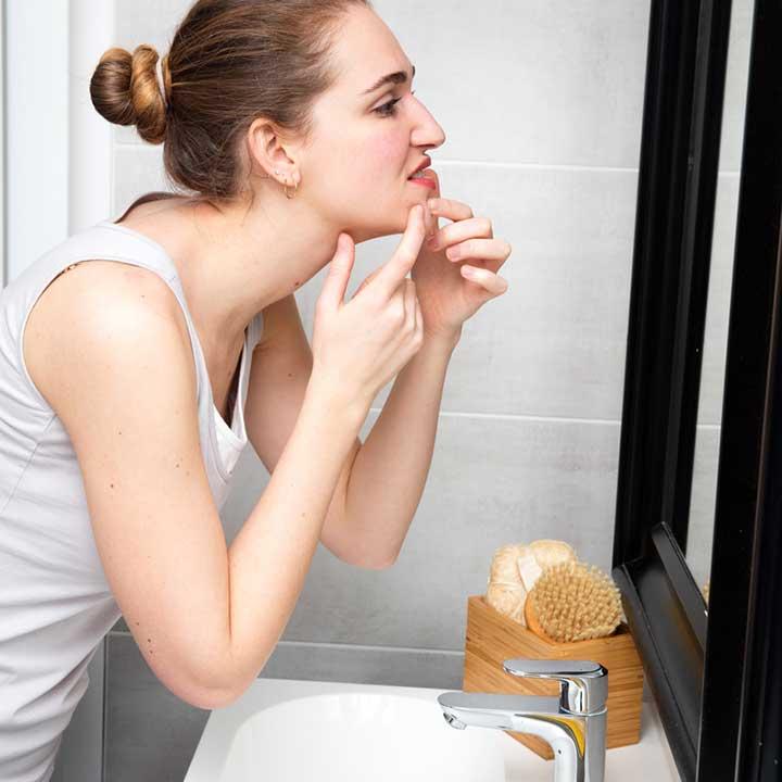 Woman taking vitamins that heal acne