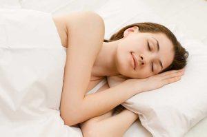 Woman sleeping to avoid lack of sleep side effects