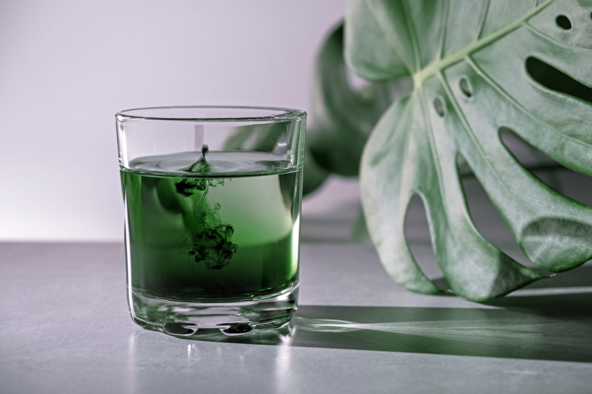 liquid chlorophyll dissolving in glass of water